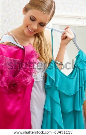 Image of pretty female looking at smart dresses while choosing a right one - stock photo