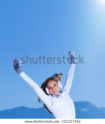 Image of pretty female with raised hands outdoors in winter, cute teenager girl jumping on the mountain, happines and freedom concept, Christmas holiday, wintertime vacation, New Year