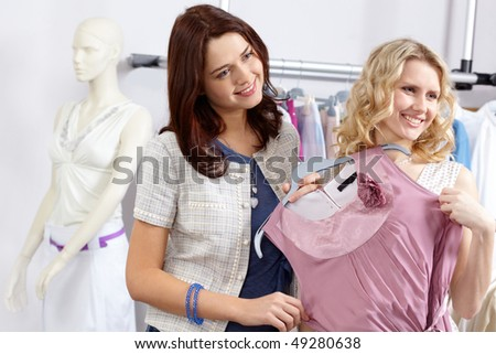 Image of pretty friends with new fashionable clothes in the department store