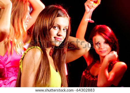 Image of pretty girl looking at camera at disco on background of her friends - stock photo