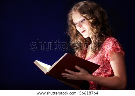 Image of pretty girl looking into open book of magic and reading it - stock photo