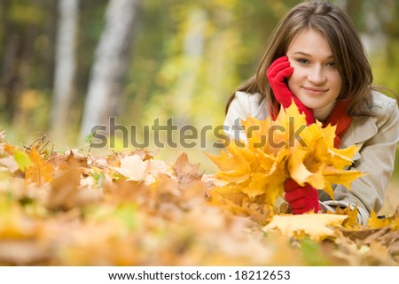 Image of pretty girl lying on ground covered with yellow dry leaves in fall