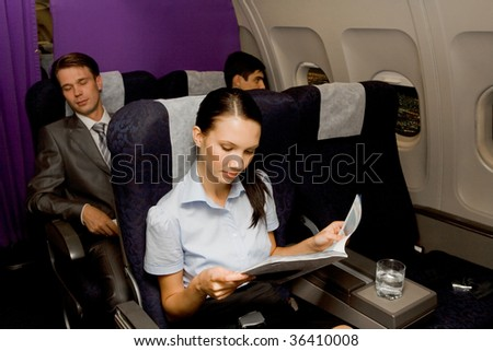 Image of pretty girl reading magazine in airplane with sleeping men behind - stock photo