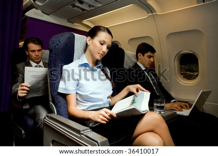Image of pretty girl reading magazine while handsome man typing next to her in airplane - stock photo