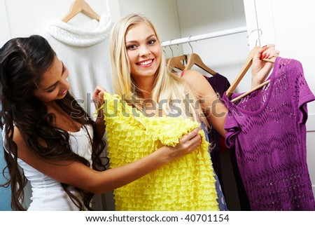 Image of pretty girl trying on smart dress on her friend - stock photo