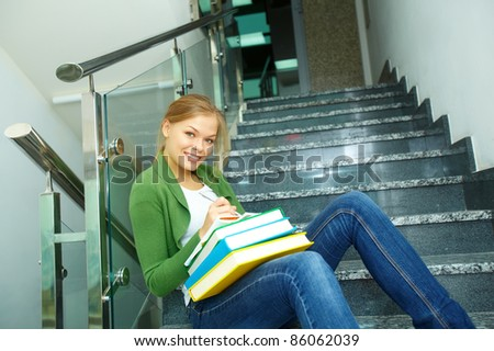 Image of pretty girl with books looking at camera in college - stock photo