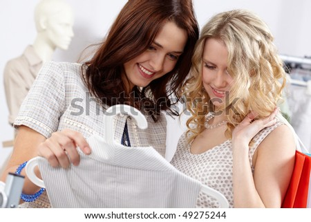 Image of pretty girls chosing clothes in the department store - stock photo