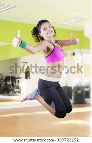 Image of pretty indian woman wearing sportswear and jumping in the fitness center while showing thumbs up