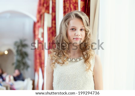 Image of pretty smiling girl posing in restaurant
