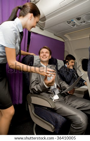 Image of pretty stewardess giving glass of water to successful businessman in airplane - stock photo