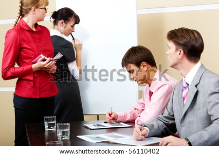 Image of pretty teacher looking at smart student by whiteboard with two men at workplaces - stock photo