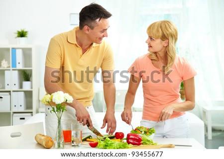 Image of pretty woman and her husband cooking salad in the kitchen
