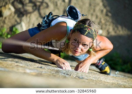 Image of pretty woman climbing on the rock - stock photo