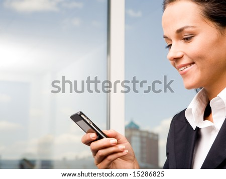 Image of pretty woman holding her mobile and sending sms