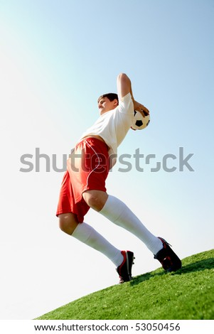Image of professional sportsman ready to throw soccer ball - stock photo