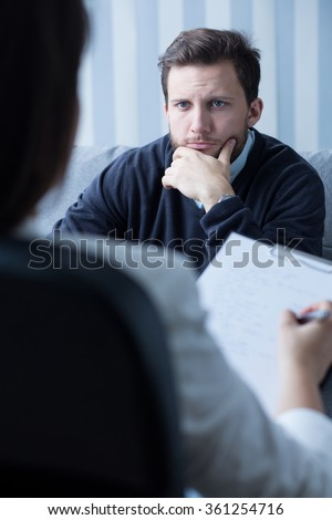 Image of psychiatrist listening to his male patient  - stock photo