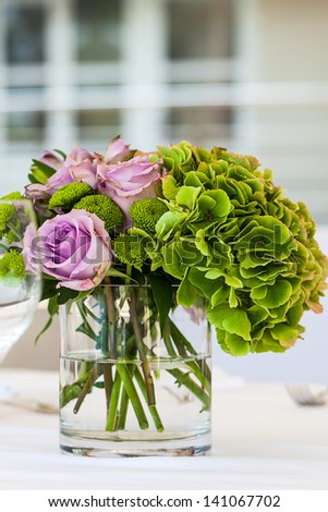 image of purple decaying roses and bright green hydrangeas in a short glass vase as center decoration for a set table - stock photo