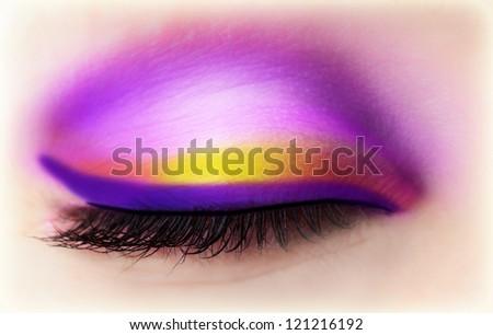 Image of purple eye makeup, one closed eyeball with beautiful violet and golden eyeshadow, face part, luxury magenta makeover, beautiful black mascara, fashionable cosmetics, beauty salon - stock photo
