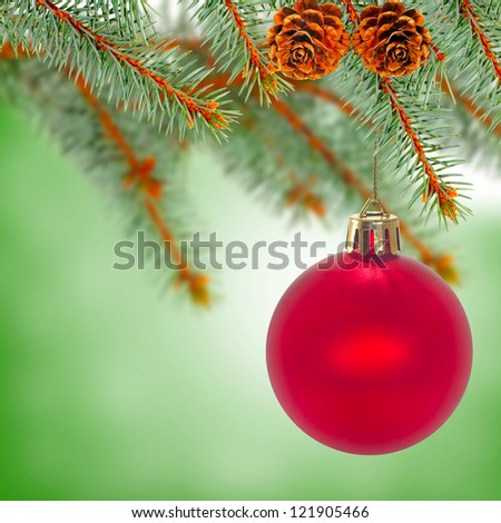 image of red Christmas ball on fir branch on a green background - stock photo