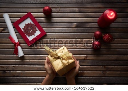 Image of red snowflake in frame, decorative toy balls, burning candle and rolled paper wrapped with red silk ribbon surrounding giftbox in female hands on wooden background - stock photo