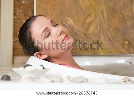 Image of relaxing woman with closed eyes having pleasant bath with seashells near by - stock photo