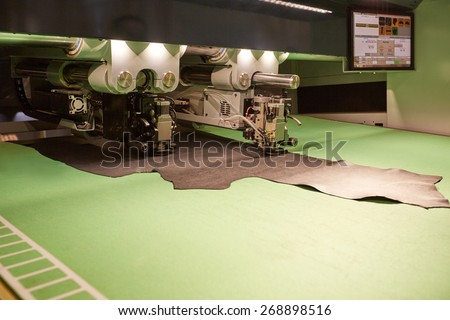 Image of robotic machine cutting leather for parts - stock photo