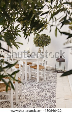Image of romantic greek restaurant in courtyard with olive trees.  - stock photo