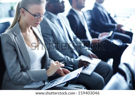 Image of row of business people working at seminar - stock photo
