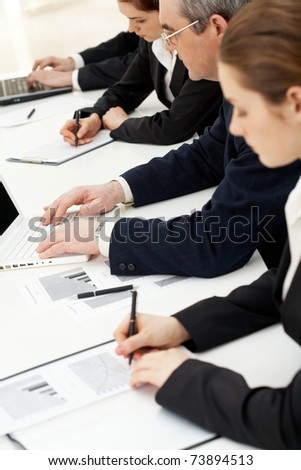 Image of row of people writing on papers and typing at briefing - stock photo