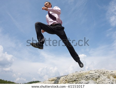 Image of running man on background of bright blue sky with white clouds - stock photo