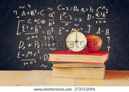 image of school books on wooden desk, apple and vintage clock over black background with formulas. education concept  - stock photo