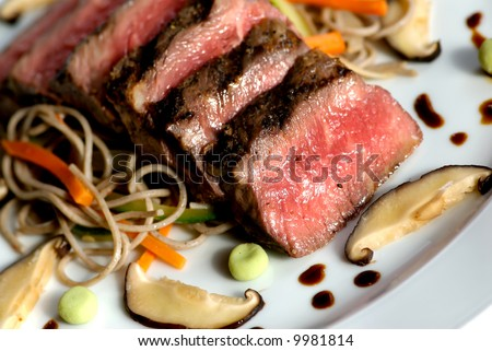 Image of seared sliced beef with vegetable garnish - stock photo