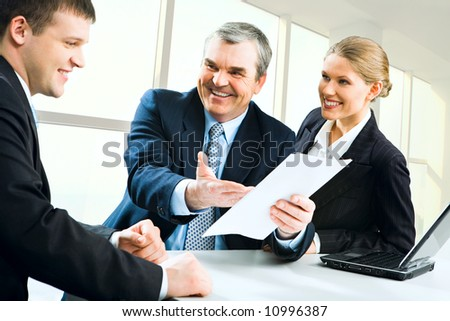 Image of senior boss giving business instructions to man and pretty secretary standing near by