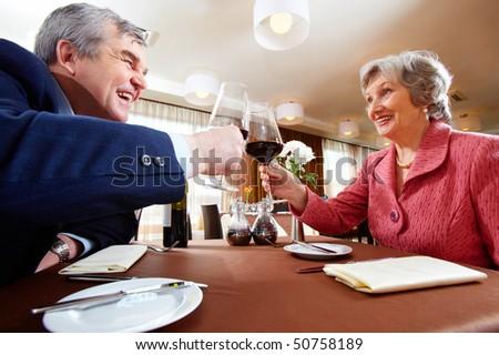 Image of senior couple celebrating at elegant restaurant - stock photo