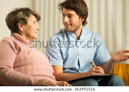 Image of senior female talking with doctor during home visit - stock photo