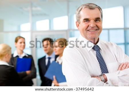 Image of senior leader smiling at camera in working environment