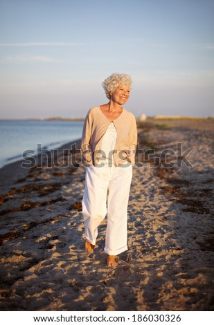 Image of senior woman walking on the beach. Happy and relaxed caucasian female strolling on the beach. - stock photo