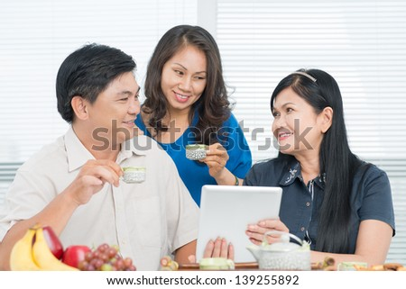 Image of seniors drinking tea and using touchpad inside