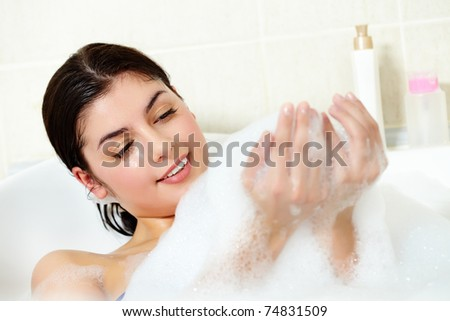 Image of serene woman having pleasant bath with foam