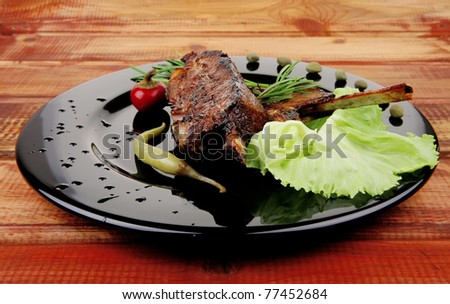image of served meat: spiced barbecued ribs on black plate with peppers chives and capers