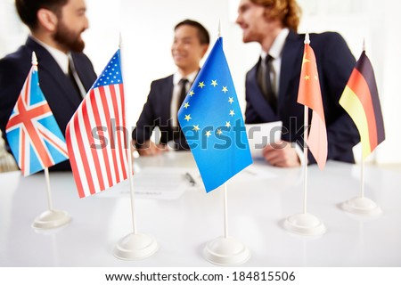 Image of several flags of different countries on workplace with three partners negotiating on background - stock photo