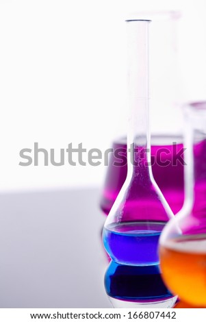 Image of several flasks with multi-color liquids in laboratory - stock photo