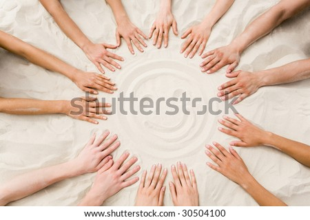 Image of several hands on sand in the form of circle with smiling face in center - stock photo