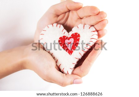 Image of sewn white heart with red decorations in woman's palms, beautiful handmade soft toy heart-shaped, romantic Valentine gift, healthy lifestyle, love and affection concept - stock photo