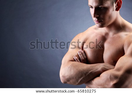 Image of shirtless man with crossed arms over dark background - stock photo