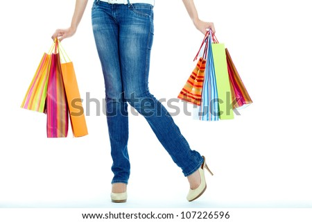 Image of shopaholic legs and shopping bags in hands - stock photo