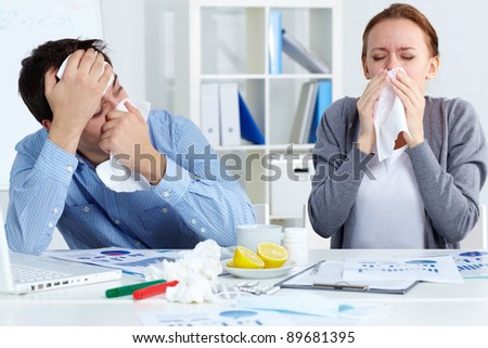 Image of sick business partners blowing their noses in office - stock photo
