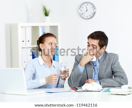 Image of sick businessman looking at his partner giving him tablets and water in office - stock photo