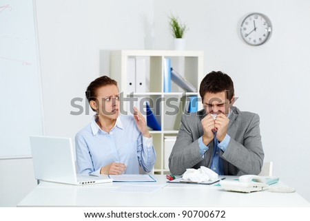 Image of sick businessman sneezing while anxious female looking at him in office - stock photo