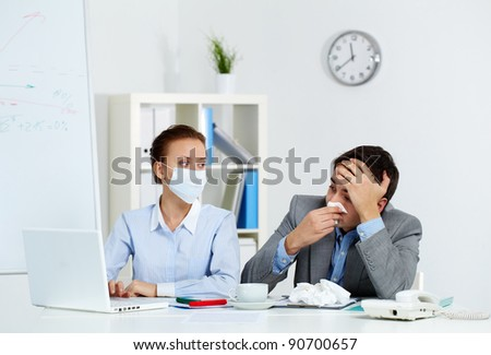 Image of sick businessman with tissue looking at laptop screen with his colleague wearing mask neaer by in office - stock photo